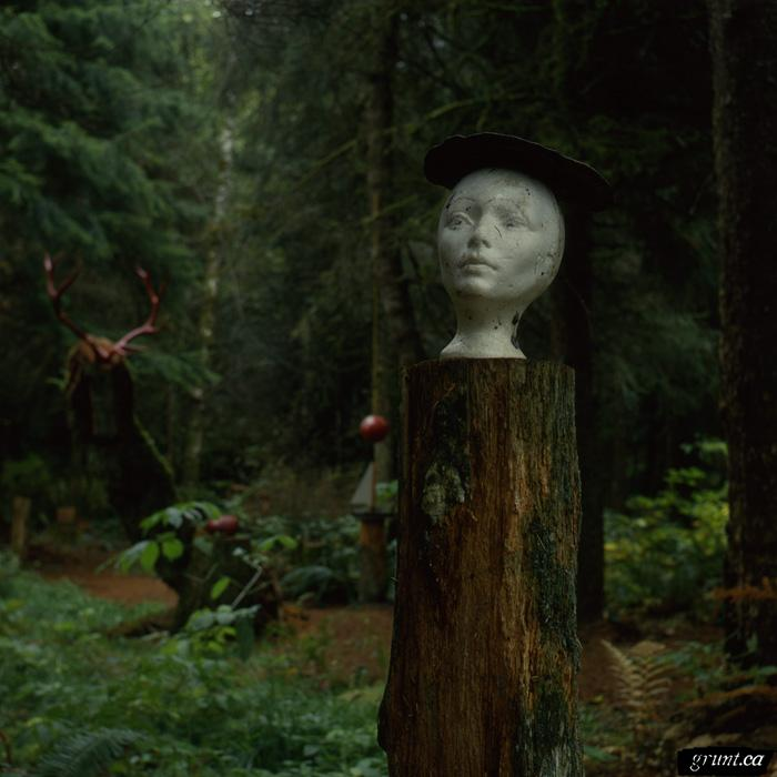 1988 03 15 Sculpture Yard Work George Sawchuck Mannequin head wearing hat atop tree trunk