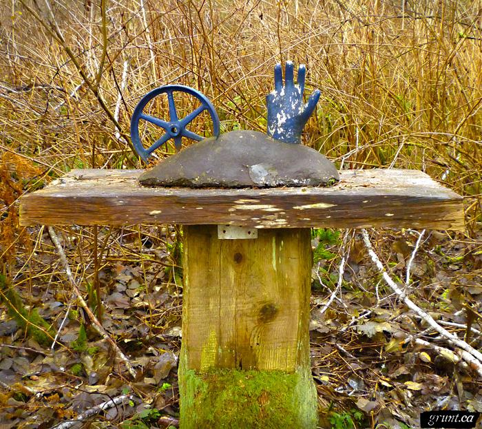 2011 12 Sculpture Yard Work George Sawchuck blue hand blue metal wheel mounted in grey form atop wood plank