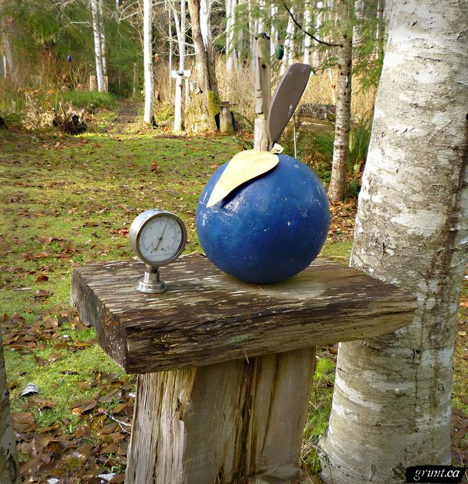 2011 12 Sculpture Yard Work George Sawchuck blue sphere with spade and pressure guage atop a wood plank