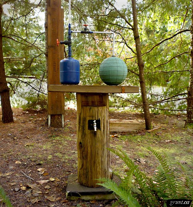 2011 12 Sculpture Yard Work George Sawchuck blue tank with red faucet connected by pipe to green rubber sphere atop a wood plank