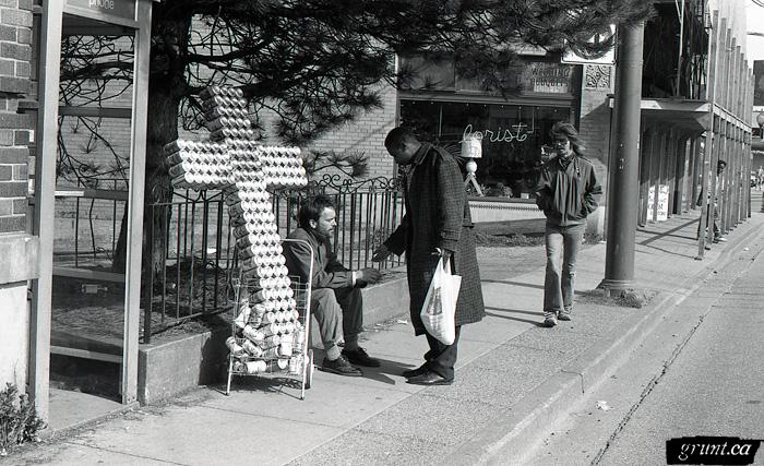 1993 04 06 Sculpture Public Works James Carl street performance Carl sitting beside road with beer can cross interacting with public