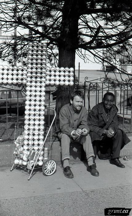 1993 04 06 Sculpture Public Works James Carl street performance Carl sitting with beer can cross and man sitting roadside